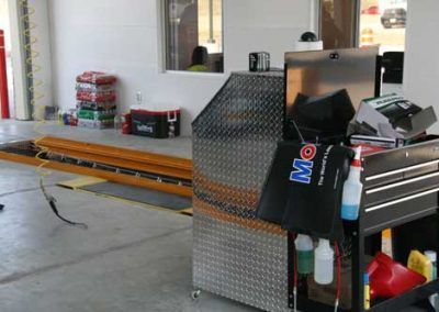 Inside of the 3-Bay Lube Center featuring a Diamond Plate covered Point of Sale Computer Terminal with the QuickPit Auto Pit System in the background