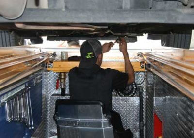 Technician working in the QuickPit Auto Servce Pit System