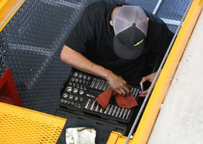 Technician working in the QuickPit Auto Service Pit, sitting putting away tools