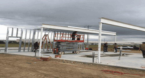 Erecting the roof panels between the wall and I-Beam using a scissor lift