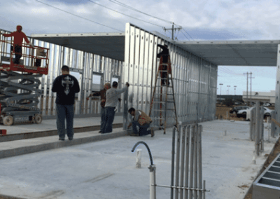 Anchoring the wall framing panel atop of the kneewall separating the car wash and the quick lube bay area