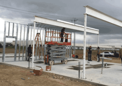 using a scissor lift to secure the roof framing panel between the wall and i-beam